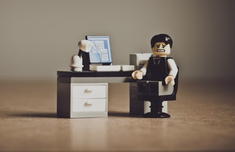 Lego man sitting at desk and looking worried